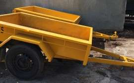 A yellow small trailer, perfect for transporting sand and soil